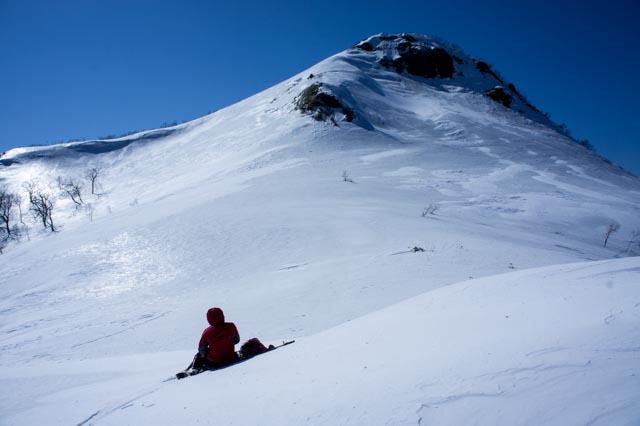 山頂直下で座り込む人